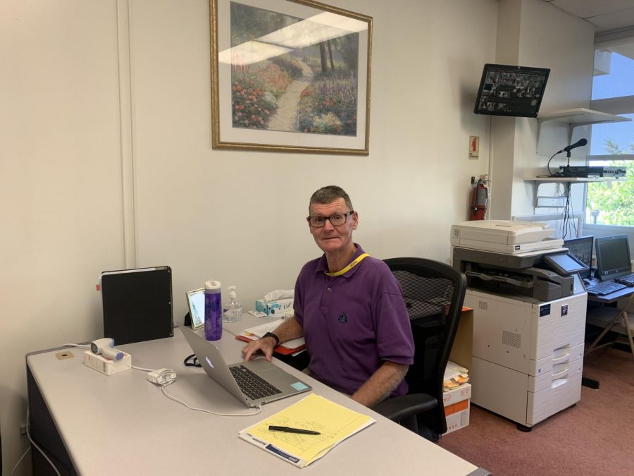 Major John Turner poses for a photo at his new desk in the main office.